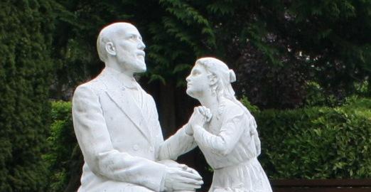 Thérèse demandant à son père, Louis, de pouvoir entrer au Carmel. Statue dans le jardin des Buissonnets, à Lisieux. (Photo : Wikimédia)
